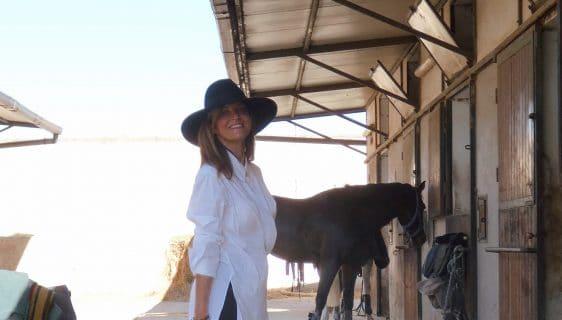 Camicia bianca donna, indossata su pantalone skinny fit nero e stivali alti tono su tono con tacco
