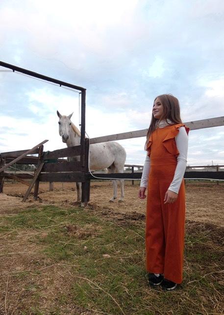Bimba con tuta jumpsuit arancione uguale e lupetto bianco indossato sotto
