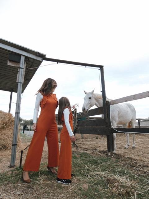 Mamma e bimba vestite uguali, con jumpsuit arancione vicino ad un cavallo bianco