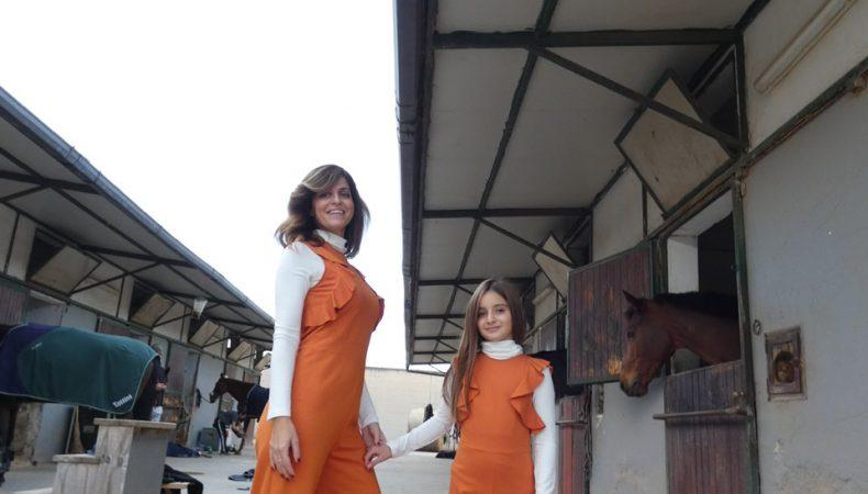 Mamma e bimba vestite uguali, con jumpsuit arancione vicino ad un cavallo marrone